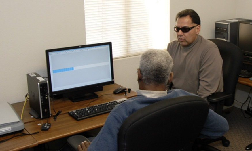 An instructor shows a student how to use a new screen reader technology. Both men are visually impaired.