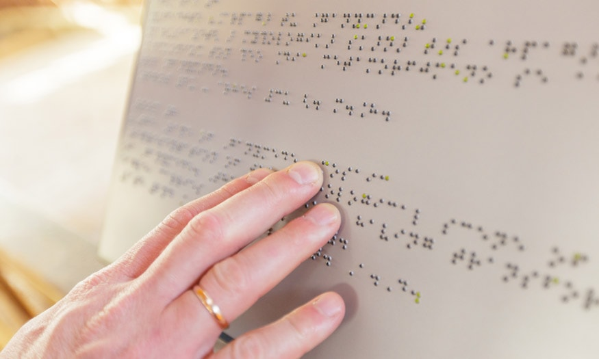 A hand reads Braille lettering.
