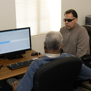 An instructor helps a student learn to use new screen reading technologies. Both men are visually impaired.